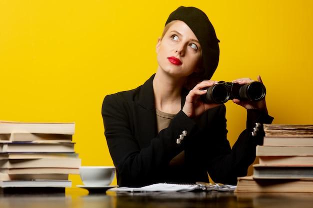 Стильная блондинка в берете сидит за столом с книгами и держит бинокль