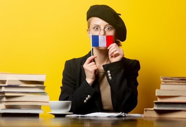Стиль блондинка в берете с французским флагом и книги вокруг на желтом