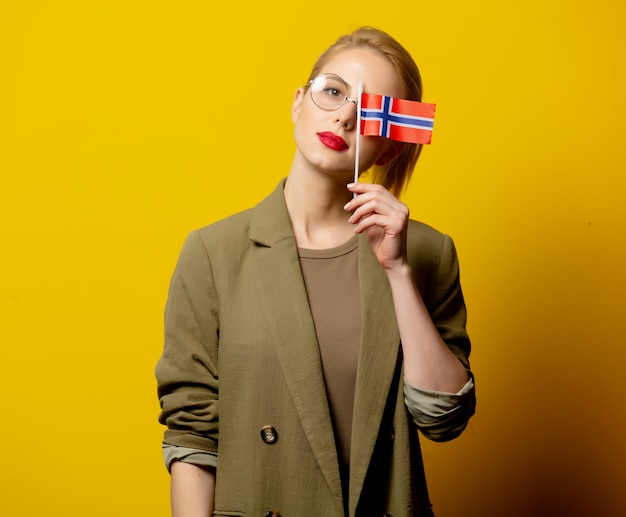 Стильная блондинка в куртке с норвежским флагом на желтом
