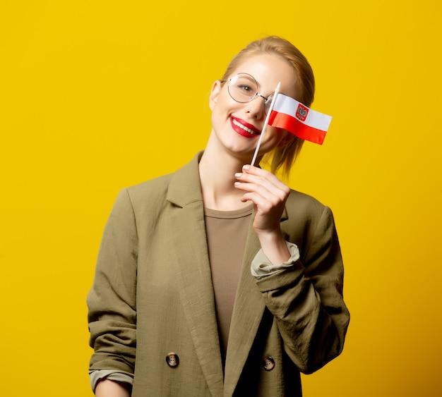 黄色のポーランドフラグ付きジャケットのスタイルのブロンドの女性