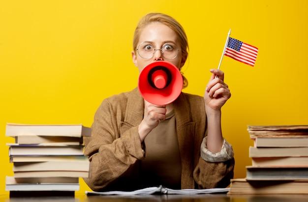 Стиль блондинка в сидя за столом с флагом сша и мегафон с книгами вокруг на желтом