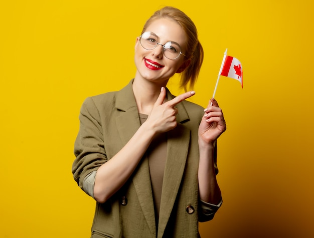 Style blonde woman in jacket with canadian flag on yellow