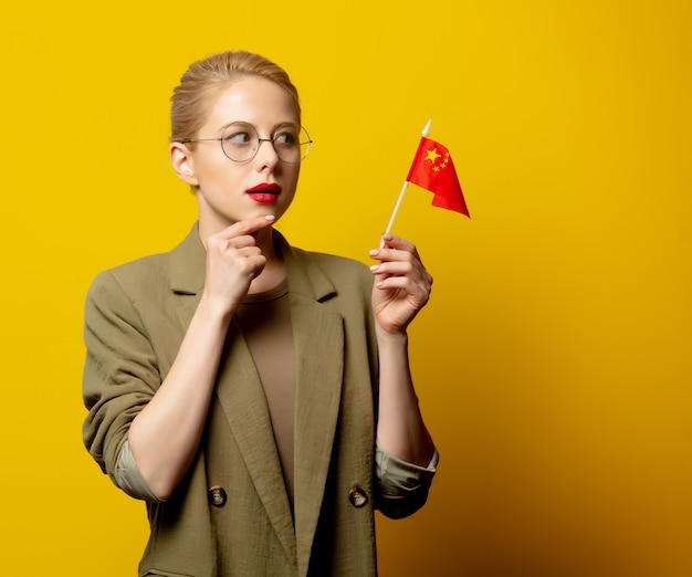 Style blonde woman in jacket with chinese flag on yellow