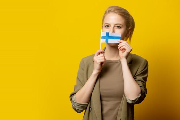 Style blonde woman in jacket with finnish flag on yellow