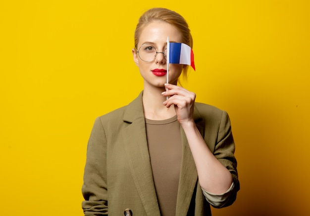 Style blonde woman in jacket with french flag on yellow