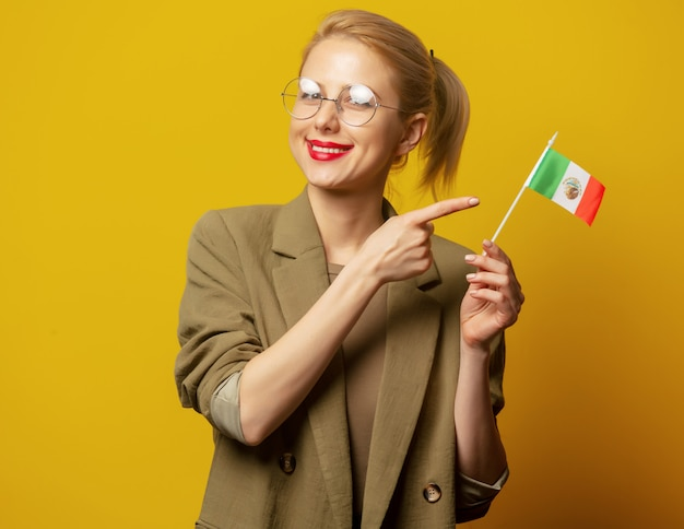 Style blonde woman in jacket with mexican flag on yellow