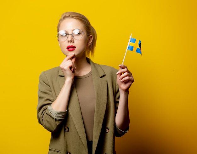 Style blonde woman in jacket with swedish flag on yellow