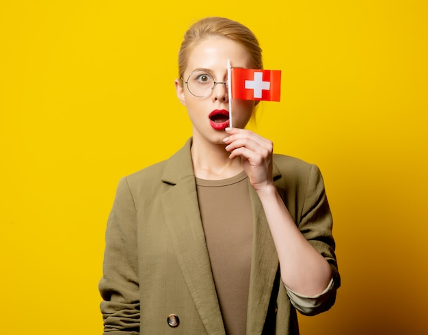 Style blonde woman in jacket with swiss flag on yellow
