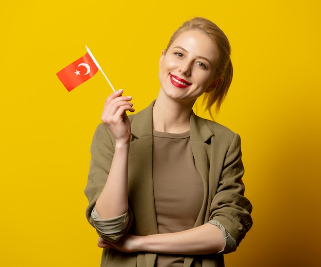 Style blonde woman in jacket with turkish flag on yellow