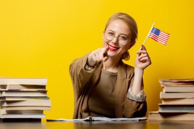 Стиль блондинке сидит за столом с книгами вокруг и держит флаг сша на желтом