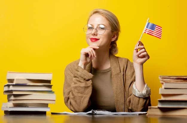 Style blonde woman sitting at table with books around and holds usa flag on yellow