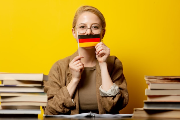 Style blonde woman sitting at table with books and flag of germany on yellow
