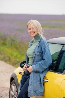 秋の時期に提出された花の近くの車で金髪の女性のスタイル