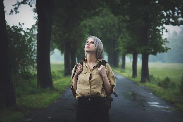 雨の日の田舎道でバックパックとスタイルのブロンドの女性