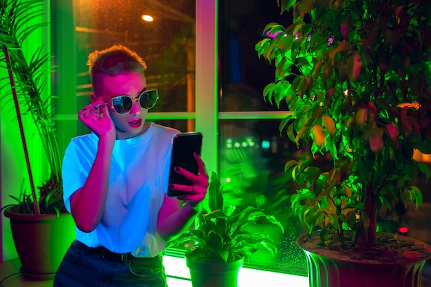 风格。时髦的妇女电影画象霓虹被点燃的内部的。像电影效果一样调子,明亮的霓虹色彩。使用智能手机的白种人模型在户内五颜六色的灯。青年文化。