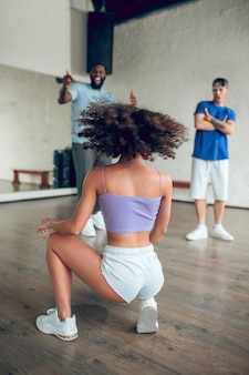 스타일, 댄스. 반바지와 운동화를 입은 소녀와 그녀의 등이 아름답게 춤추는 모습과 친구들