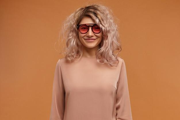 스타일, 패션 및 청소년 개념. 세련된 블라우스와 눈 그늘을 입고 포즈를 취하는 지저분한 분홍빛 머리를 가진 사랑스러운 유행 찾고 젊은 유럽 여자