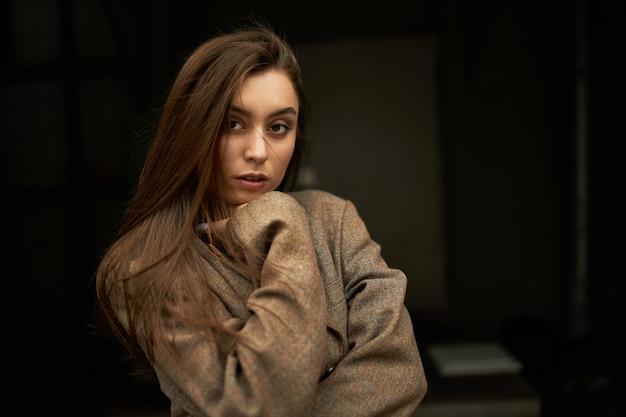 스타일, 패션, 아름다움 및 여성 성 개념. 심각한 자신감 표정으로 카메라를보고 느슨한 갈색 머리를 가진 사랑스러운 화려한 젊은 여성, 특대 재킷이나 코트를 입고