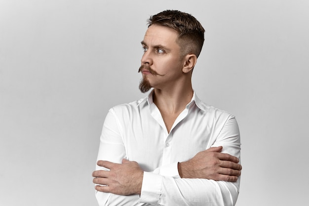 Stile, moda e concetto di business. studio immagine di fiducioso elegante giovane imprenditore europeo con eleganti baffi e barba incrocio le braccia sul petto e guardando lontano, avendo uno sguardo pensieroso