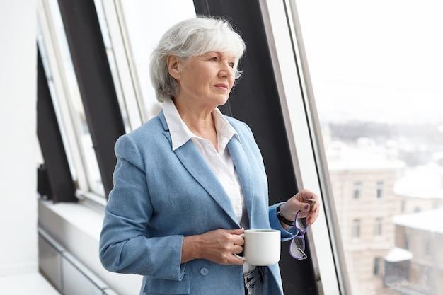 스타일, 패션, 경력 및 연령 개념. 안경과 머그잔을 들고 커피를 마시고 창문을 통해보고 잠겨있는 사려 깊은 표정을 가진 그녀의 60 년대에 성공적인 우아한 회색 머리 여성