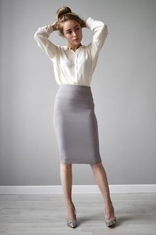 Concetto di stile, moda e vestiti. immagine visiva della splendida giovane donna di affari alla moda in abbigliamento formale elegante che si prepara per il lavoro, facendo il panino dei capelli, con un'espressione facciale seria