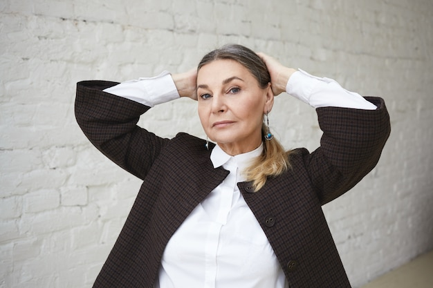 Style and fashion concept. horizontal isolated shot of serious successful 55 year old caucasian businesswoman with gathered hair holding hands behind her head, staring with confident look