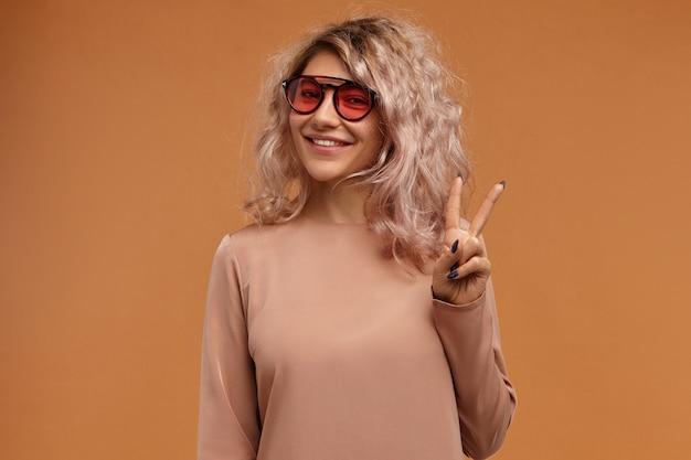 Stile, tendenze della moda e concetto di gioventù. foto di ragazza alla moda hipster indossando occhiali da sole alla moda con lenti rosa con un ampio sorriso gioioso, facendo segno di pace