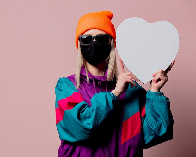 Style girl in 80s sportsuit and black face mask hold heart shape banner on pink wall