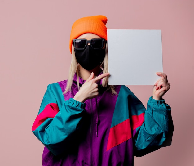Style girl in 80s sportsuit and black face mask hold white square on pink wall