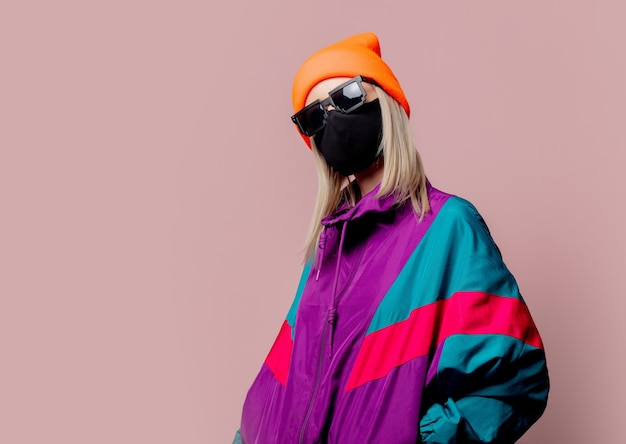 Style girl in 80s sportsuit and black face mask on pink wall