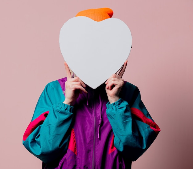 Style girl in 80s sportsuit hold heart shape on pink wall