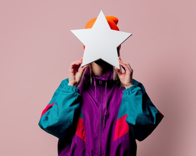 Style girl in 80s sportsuit hold star shape banner on pink wall