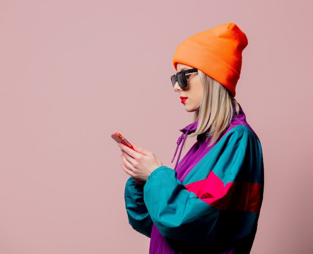 Style girl in 80s sportsuit and sunglasses hold mobile phone on pink wall