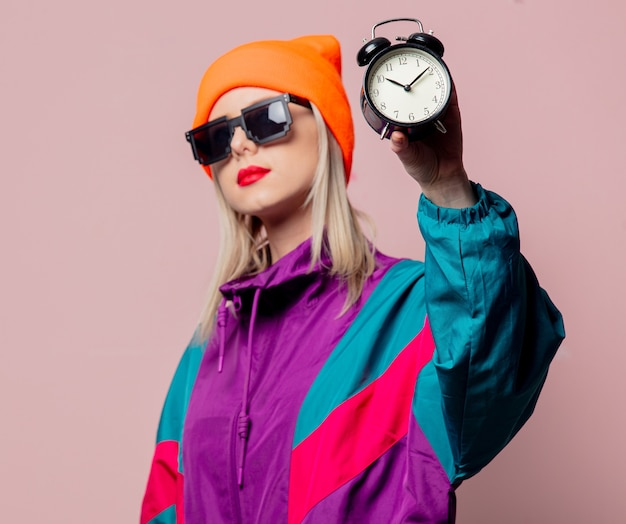 Style girl in 80s sportsuit and sunglasses hold vintage alarm clock on pink wall