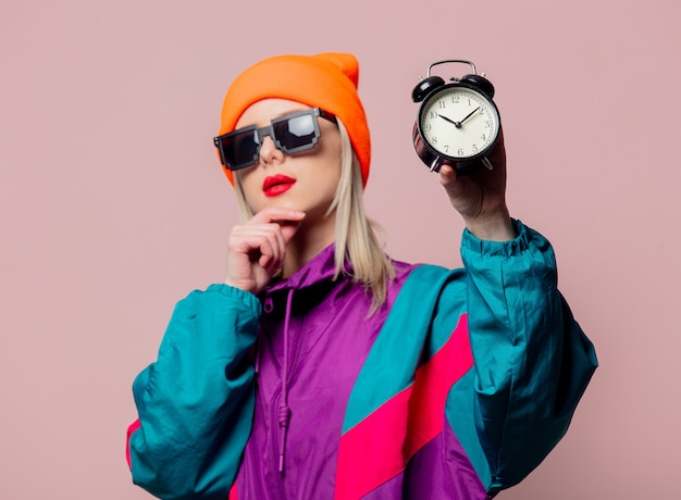 Style girl in 80s sportsuit and sunglasses hold vintage alarm clock on pink wall Premium Photo