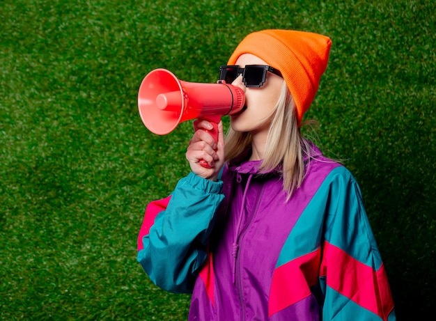 Style girl in 80s sportsuit with megaphone on green grass wall