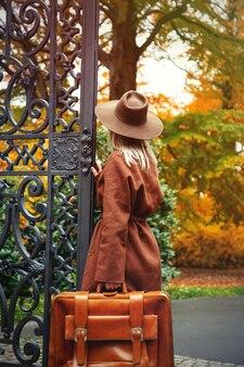 Стильная девушка в коричневом пальто с чемоданом в осеннем парке возле ворот