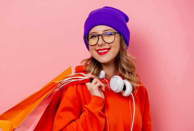Style girl in orange hoodie and purple hat with shopping bags on pink wall