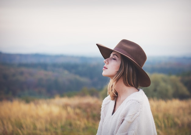 Style girl in sweater and hat at countryside with mountains on background