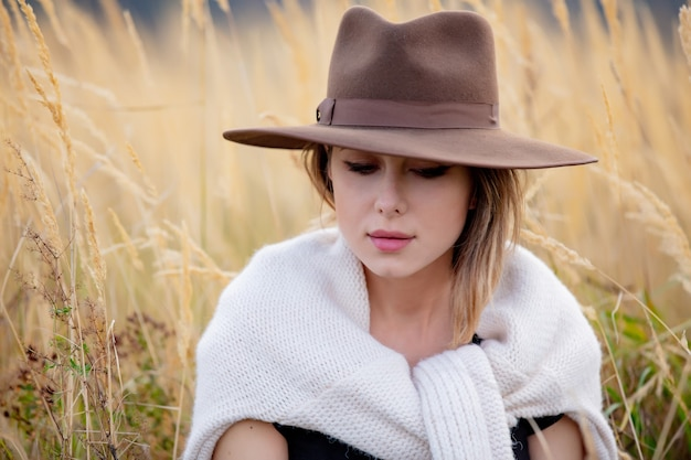 Style girl in sweater sits in yellow grass at countryside with mountains on background