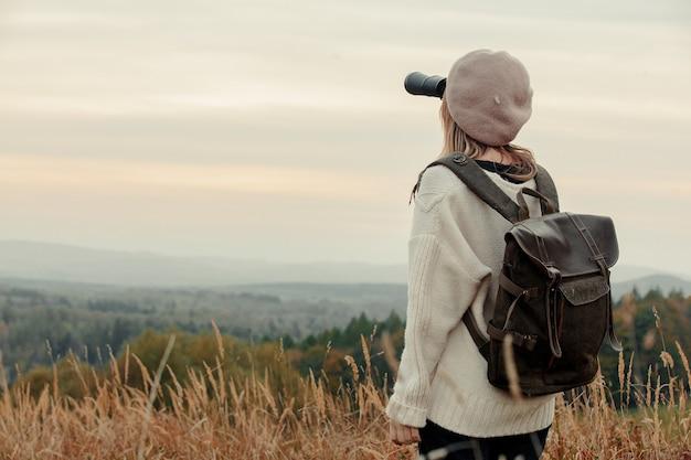 배경에 산이 있는 시골에서 쌍안경과 배낭을 든 스타일 소녀