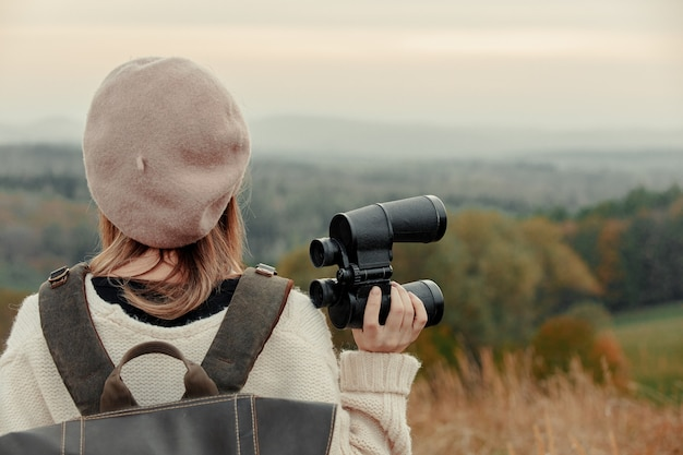 Style girl with binoculars and backpack at countryside with mountains on background