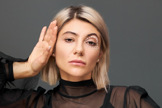 Style, glamour, cosmetics and beauty concept. portrait of stunning young female in black transparent blouse posing isolated touching face, wearing face piercing, dyed short haircut and trendy make up