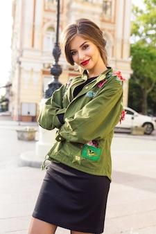 Стильная великолепная женщина идет по улице в стильном наряде