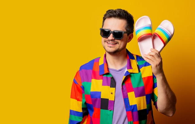 Style guy in 90s shirt and pixel sunglasses holds flip flops