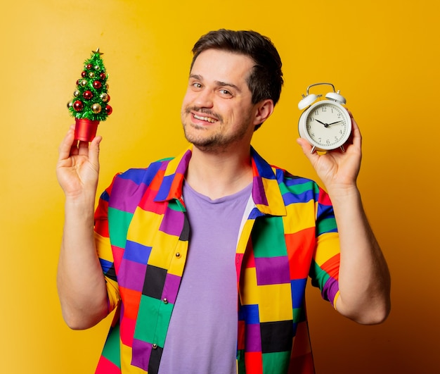 Style guy in 90s shirt with christmas tree and alarm clock