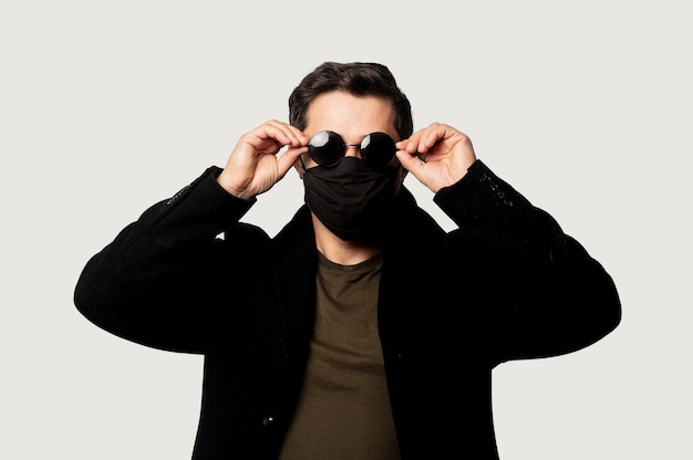 Style guy in black coat, face mask and sunglasses