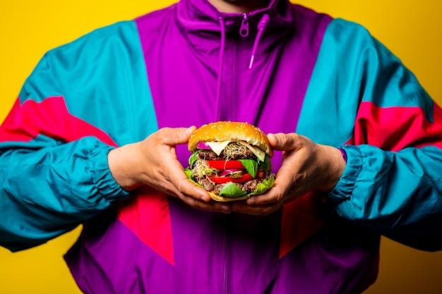 Стиль парень в одежде 80-х с большим гамбургером