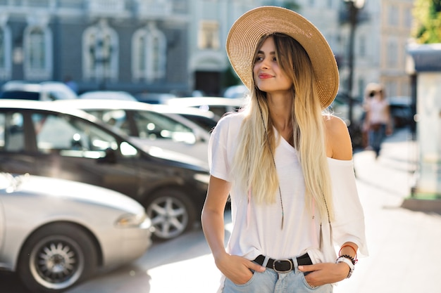 스타일 행복 한 여자는 거리에서 재미가 있습니다. 예쁜 젊은 여자는 햇빛에 걷고있다.