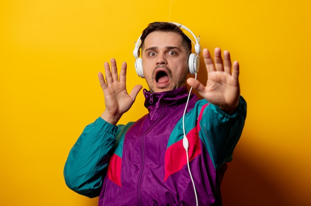 Style man in 90s tracksuit with headphones on yellow wall